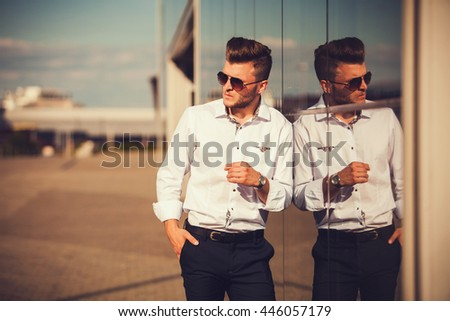 casual young man standing with a hand in his pocket outdoors - stock photo