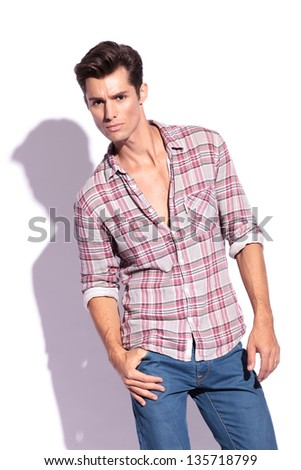 casual young man standing with a thumb in his pocket and looking straight into the camera. isolated on white background - stock photo