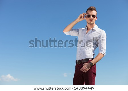 casual young man stands outdoor with a hand in his pocket and with the other adjusting his sunglasses while looking at the camera