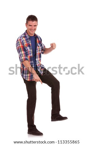 Casual young man stepping on something, pointing at it and smiling. Young man posing like Goliath, showing his superiority - stock photo