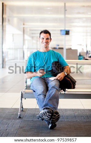 casual young man waiting for flight at airport
