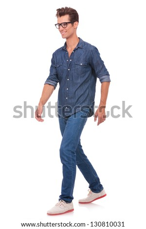 casual young man walking and looking forward, away from the camera, with a smile on his face. isolated on a white background - stock photo