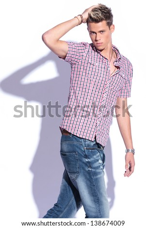 casual young man walking and putting a hand in his hair while looking at the camera. on white background with shadow