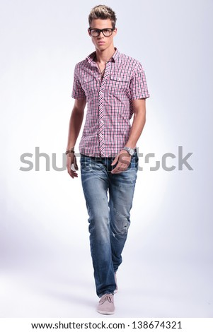 casual young man walking forward in the direction of the camera, looking very serious. on gray background