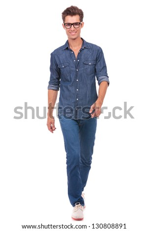 casual young man walking in your direction and smiling. isolated on a white background - stock photo