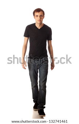Casual young man walking. Studio shot over white. - stock photo