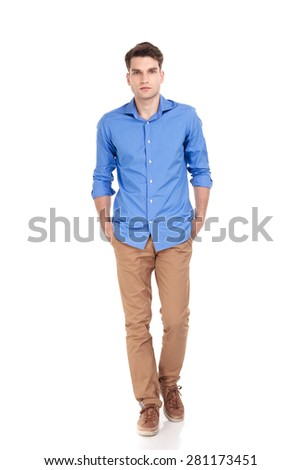 Casual young man walking with his hands in pockets on isolated background. - stock photo