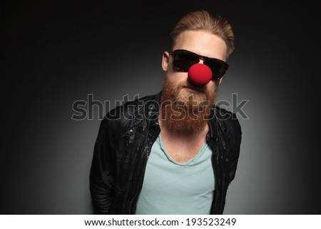 casual young man with a long beard and a clown red nose looking into the camera with his hands at the back. on a dark studio background - stock photo