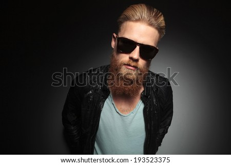 casual young man with a long beard and sunglasses looking into the camera. on a dark studio background