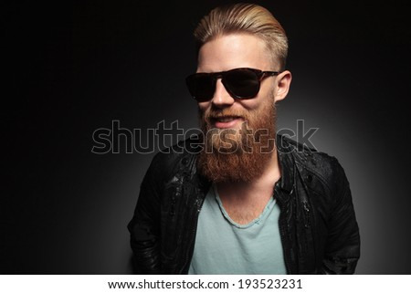 casual young man with a long beard smiling for the camera. on a dark studio background - stock photo