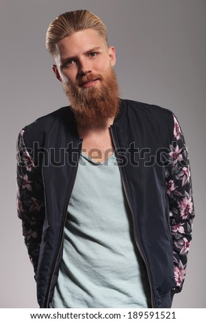 casual young man with a long red beard looking into the camera with a smile on his face while holding hands in back pockets. on gray studio background - stock photo