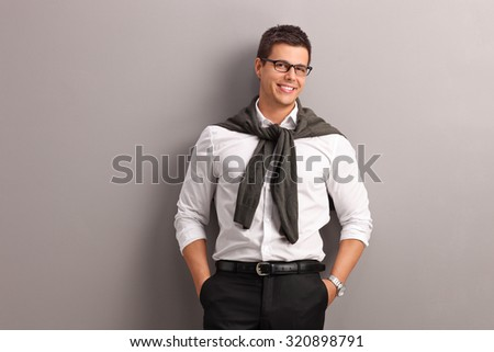 Casual young man with his sweater tied around his shoulders leaning against a wall and looking at the camera