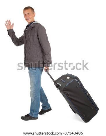casual young man with suitcase waving hello, full length, white background