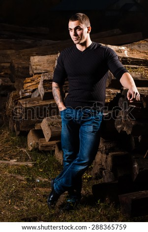 casual young man with tattoo sitting indoors - stock photo
