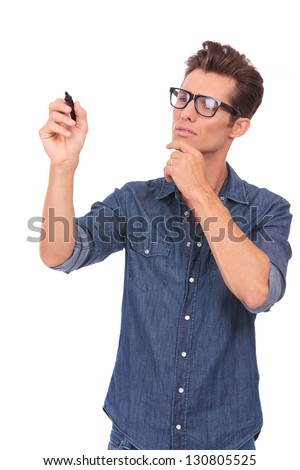 casual young man writing something on an imaginary screen and looking pensively at it. isolated on a white background - stock photo