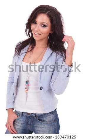 casual young woman holding her hair and the other hand in her pochet while smiling to the camera. on white background