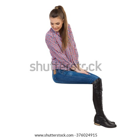 Casual young woman in lumberjack shirt, jeans and black boots sitting on a top and looking down. Side view. Full length studio shot isolated on white. - stock photo