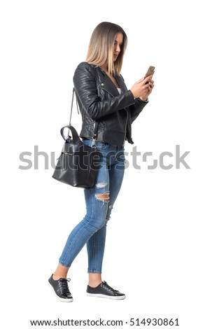 Casual young woman in street style clothing walking and typing on mobile phone. Full body length portrait isolated over white background