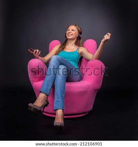 Casual young woman listening to mp3 player. front view of brunette girl sitting in armchair - stock photo