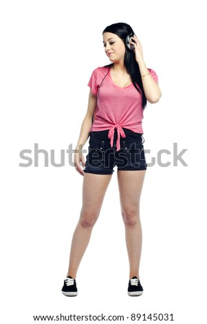 Casual young woman listening to music with head phones on - stock photo