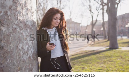 Casual young woman portrait listening to music in a park. Filtered image with back light effect.