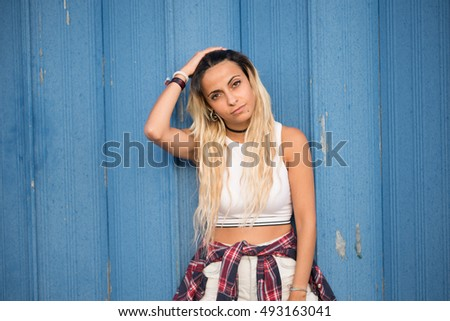 Casual young woman portrait over blue wall outdoors