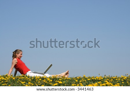 Casual young woman relaxing with laptop outdoors, in a flowering dandelion field. - stock photo
