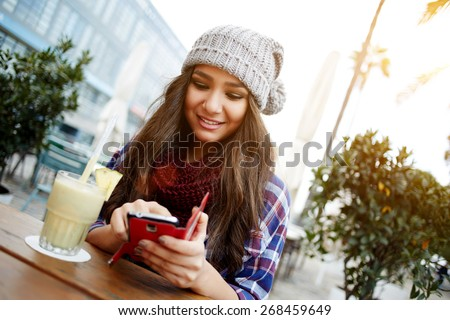 Casual young woman sending text message while sitting at a sidewalk cafe in the city, charming hipster girl enjoying a fresh cocktail during her break or holiday, female student chatting on cell phone - stock photo