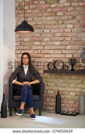Casual young woman sitting in armchair at home, looking at camera. - stock photo
