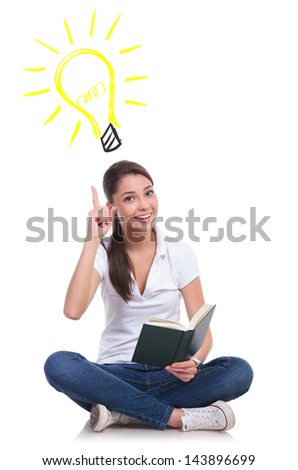 casual young woman sitting with legs crossed and having an idea while holding a book, pointing up at  a light bulb while looking at the camera. isolated on white background