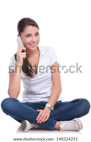 casual young woman sitting with legs crossed and talking on the phone while smiling to the camera. isolated on white background - stock photo