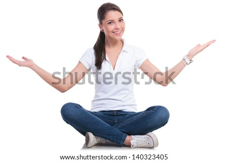 casual young woman sitting with legs crossed and welcoming you. isolated on white background - stock photo