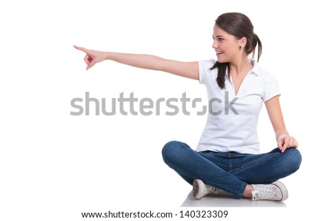 casual young woman sitting with legs crossed pointing and looking to her side with a smile. isolated on white background - stock photo