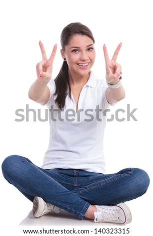 casual young woman sitting with legs crossed showing victory sign with both hands while smiling to the camera. isolated on white background - stock photo