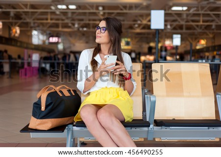 Casual young woman using her cell phone while waiting to board a plane at the departure gates.  - stock photo