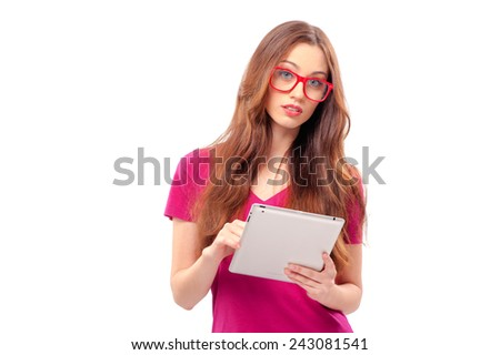 Casual young woman with red glasses holding tablet computer isolated on white background. working on touch screen. - stock photo