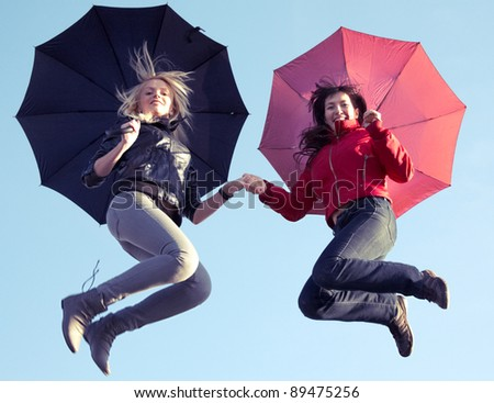 Casual young women with umbrellas having fun outdoor at autumn