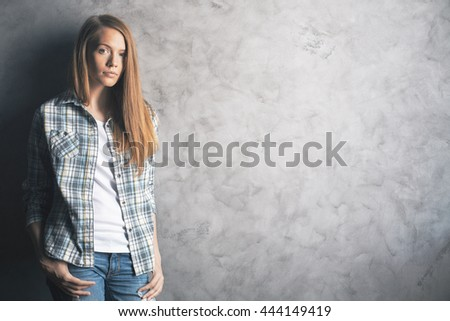 Casually dressed, attractive young woman standing against blank concrete wall. Mock up - stock photo