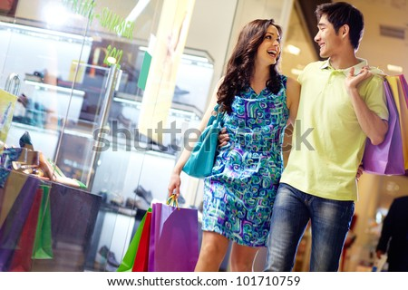Casually dressed beautiful couple walking through the mall carrying a lot of shopping bags - stock photo