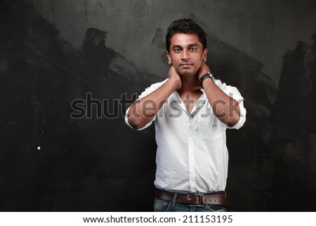 Casually dressed Indian young man against a black wall - stock photo