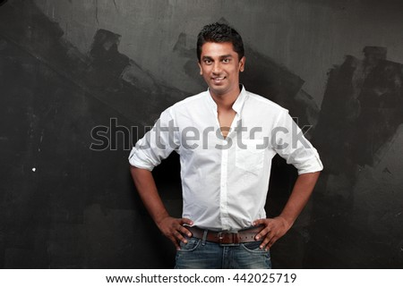 Casually dressed Indian young man against a dark wall - stock photo