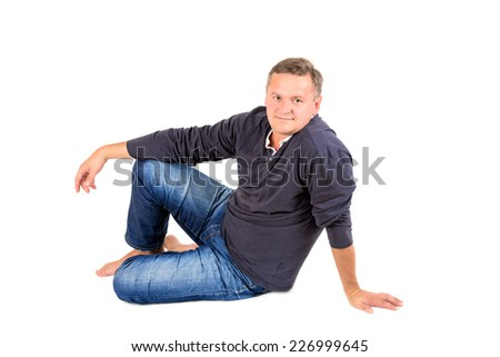 Casually dressed middle aged man barefoot sitting on a floor. Man shot in horizontal format isolated on white. - stock photo