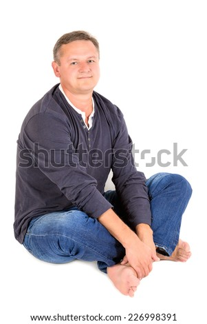 Casually dressed middle aged man smiling. Sitting on a floor man shot in vertical format isolated on white. - stock photo