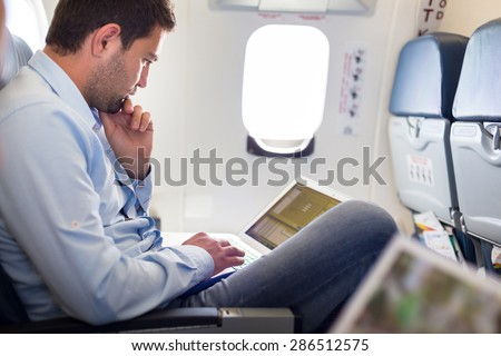 Casually dressed middle aged man working on laptop in aircraft cabin during his business travel. Shallow depth of field photo with focus on businessman eye. - stock photo