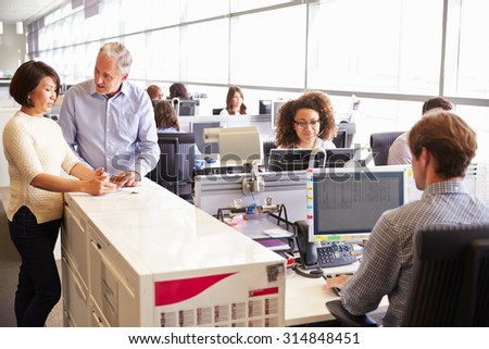 Casually dressed staff standing in a busy open plan office - stock photo