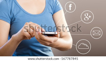 Casually dressed woman in blue shirt using her touchscreen smartphone for cloud or social sharing - stock photo