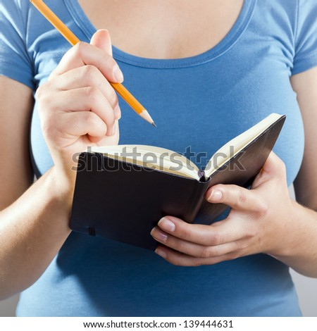 Casually dressed woman in blue shirt writing with a pencil in a small black notebook - stock photo