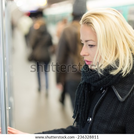 Casually dressed woman wearing winter coat,buying metro ticket at the ticket vending machine. Urban transport.