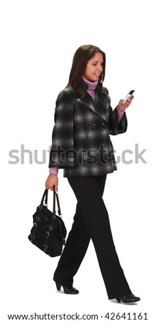 Casually dressed woman with a bag, walking while is checking her mobile phone,isolated against a white background.