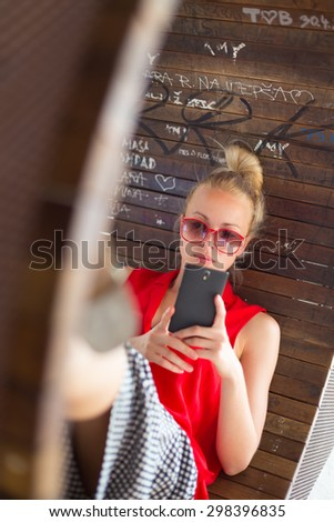 Casually dressed young cheerful lady wearing red sunglasses playing carelessly with her android smarthphone browsing trough social networks relaxing on  contemporary circular bench in city park. - stock photo